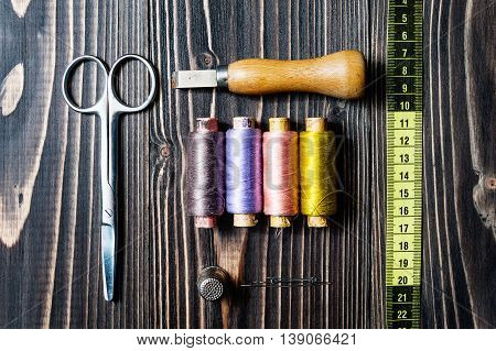 Accessories for sewing on dark wooden table - seam ripper, thread, scissors, centimeter, measuring tape.