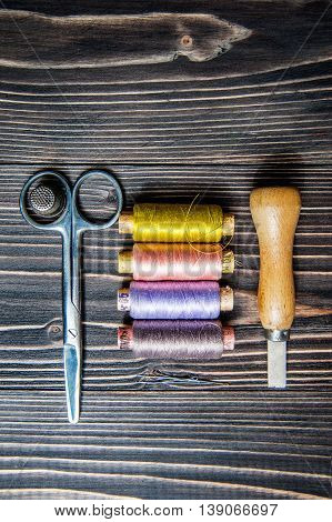 Accessories for sewing on dark wooden table - seam ripper, thread, scissors.