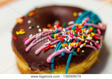 A close up of a doughnut with chocolate icing colorful sprinkles and drizzled blue and pink icing.