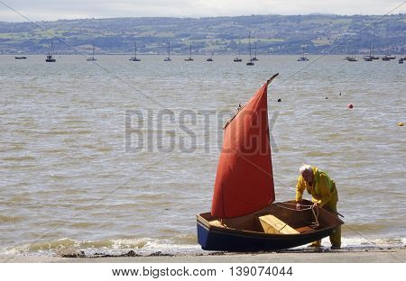 WEST KIRBY, ENGLAND, JULY 4. The River Dee on July 4, 2016, at West Kirby, England. At high tide a man in yellow safety gear prepares his dinghy for sailing on the River Dee at West Kirby England. The coast of Wales is in the background.