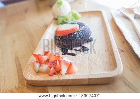 chocolate lava cake with vamilla ice cream and strawberry. chocolate lava on wood plate. chocolate lava. Hot chocolate pudding with fondant centre.(selective focus)