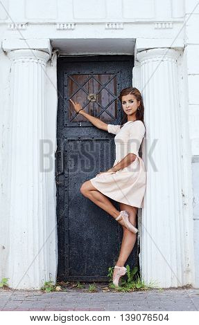 Ballerina at the entrance of the old mansion in summertime