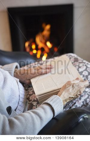 Detail Of Senior Woman Reading Book By Fire At Home