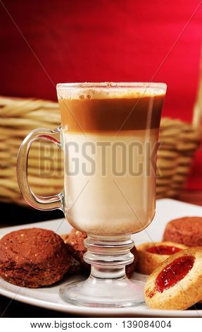 Capuchino coffe and cookies in a plate with red background