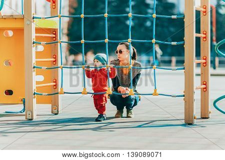 Mother and son on the Playground walk around the children's constructions the boy stands and holds onto the rope ladder the mother supports the child