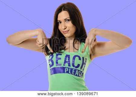 slim woman in a green shirt points to print isolated on purple