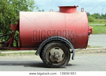 large red watering barrel for watering streets hitched to the tractor in the Gatchina, Leningrad region