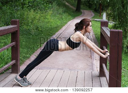 Young woman doing stretching outdoors in the afternoon. In the park.