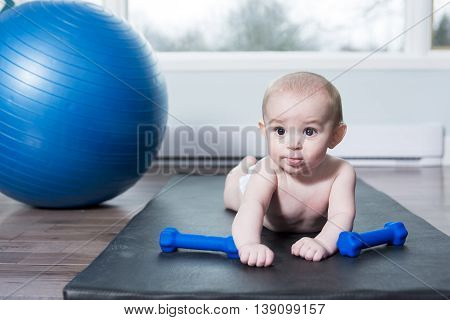 A cute baby doing exercises with ball at home