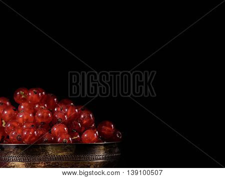 red currant in old silver cup in dark food photography style with black copyspace
