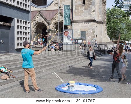 BERLIN GERMANY - JULY 19 2016: Artist with soap bubbles and tourists in front of Gedachtniskirche in Berlin Germany