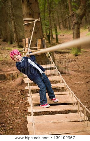 Adorable small kid boy in a red hat and sneakers standing on the wooden pathway in the forest. Outdoor activities with a child. Unstable walking on the wooden bridge. Nature in the forest.