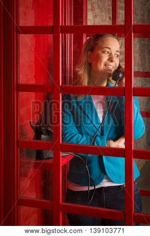 Pretty blond woman in a blue jacket calling on the retro phone. Girl with an old telephone in the red phone booth in English style. Lady with a black handset. Vintage telephone.