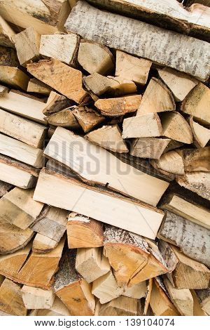 Firewood background - chopped firewood on a stack. Dry chopped firewood logs in a pile. Nature abstract background with stack of firewood.