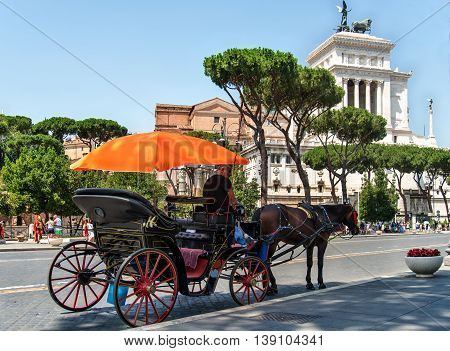 ROMA ITALY JULY 3 2016 : Coachman sits on a carriage pulled by a horse waiting for tourists. Imperial fora street