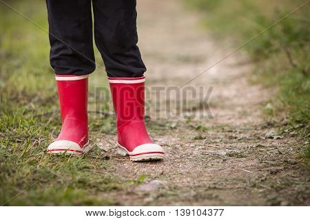 little kid boy in rain rubber boots. leg shot. Child in bright red shoes. On a countryside road outdoors.