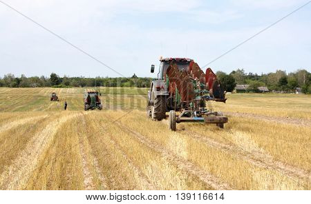 after harvesting the tractor with working plows went to raise the plow
