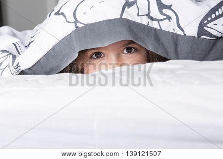 A Child or teen under covers in bed