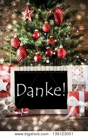 Christmas Card For Seasons Greetings. Christmas Tree With Balls And Snowflakes. Gifts Or Presents In The Front Of Wooden Background With Bokeh Effect. Chalkboard With German Text Danke Means Thank You