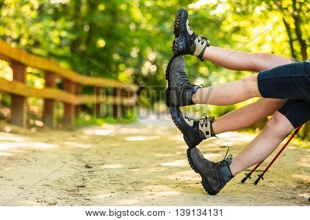 Travel trekking leisure holiday concept. Couple having fun waving legs. Two people outdoor in hiking boots enjoy time.