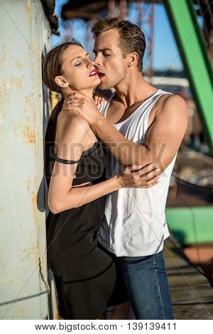 Attractive couple with closed eyes shows their passion in the industrial zone. Guy wears a white singlet and blue jeans, girl wears a black dress. Outdoors. Vertical.