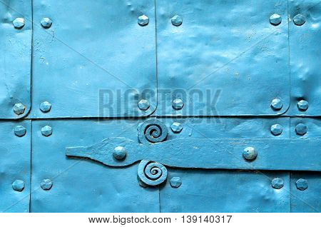 Metal light blue surface of old hammered metal plates with metal rivets and architectural details on them. Metal bright blue industrial background.