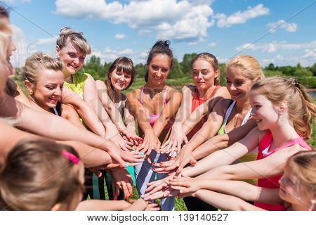 Group of fit women putting their hands together