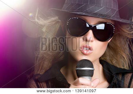 Beautiful woman singing karaoke in spotlight