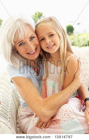 Portrait Of Grandmother With Granddaughter Relaxing Together On Sofa