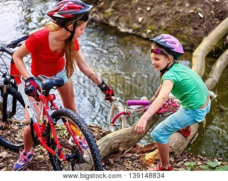 Bikes bicycle girl. Children with bicycle to help each other to cross river on log. Girl rides bicycle. Girl bicycling fording throught water . Bicycle trip is good for health.