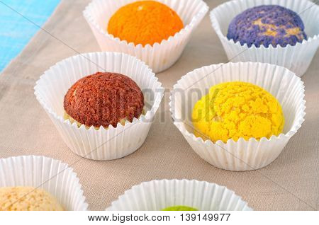 Set of different colorful cake shu eclairs close up on a blue wooden table with copy space