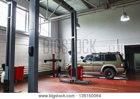 Modern repair shop with SUV on maintenance. Professional car diagnostics in big auto service
