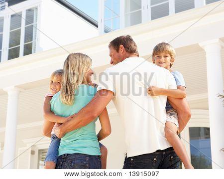 Jonge familie staande buiten huis van de droom