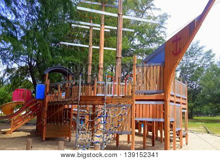 Thai ship-shaped wooden jungle gym with nets, slides, masts, boat prow, under pine trees at beach playground, Songkhla, Thailand