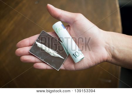drug use, people, addiction and substance abuse concept - close up of addict hand with crack cocaine drug dose track on mirror and money roll