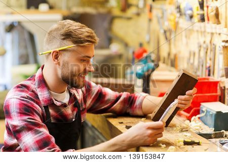 profession, carpentry, woodwork and people concept - carpenter with wood plank and notebook checking his notes at workshop