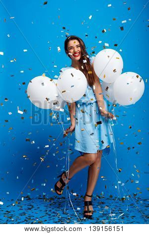 Portrait of young beautiful brunette girl in dress looking at camera, holding baloons, smiling, laughing, resting at party over blue background.