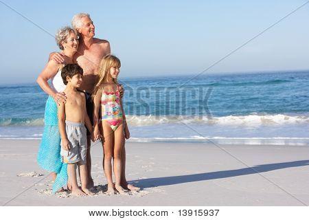 Grandparents And Grandchildren Standing On Sandy Beach