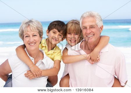 Grandparents And Grandchildren Relaxing On Beach Holiday