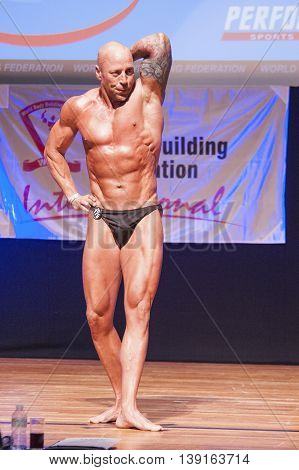 MAASTRICHT THE NETHERLANDS - OCTOBER 25 2015: Male bodybuilder Erik Stobbe flexes his muscles and shows his best physique in a abdominal and thighs pose on stage at the World Grandprix Bodybuilding and Fitness of the WBBF-WFF on October 25 2015 at the MEC