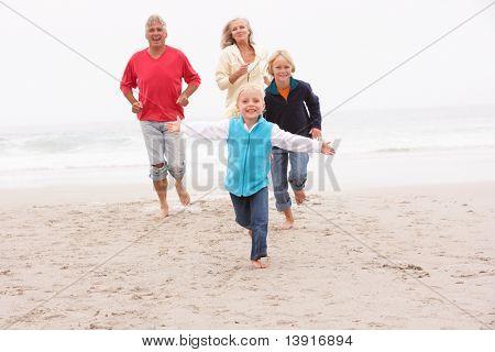 Grandparents And Grandchildren Running On Winter Beach Together