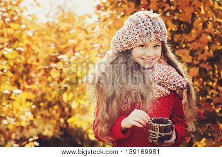 happy child girl on autumn walk in forest with handmade rustic jar