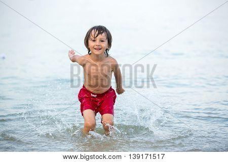 Cute Boy, Splashing Water On The Beach