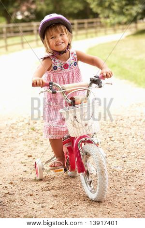 Girl Learning To Ride Bike Wearing Safety Helmet
