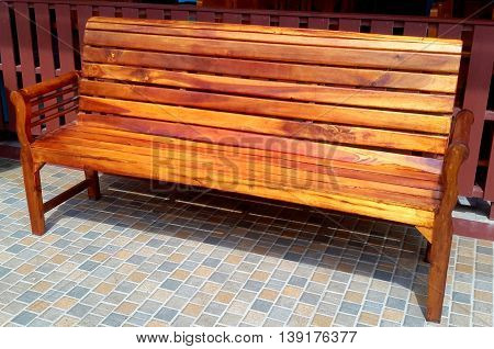 polished hardwood bench with arm rests on blue tile floor, against slatted board wall, Songkhla, Thailand