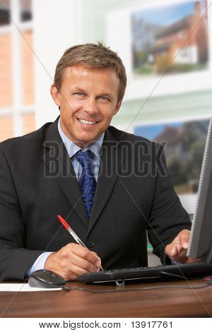Male Estate Agent Working At Desk