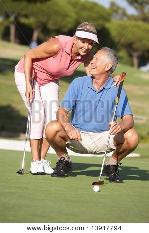 Senior Couple Golfing On Golf Course Lining Up Putt On Green poster