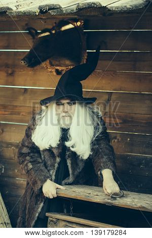 Brutal druid old man with long silver hair and beard in black Halloween hat opens vintage wooden chest on log house background