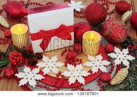 Christmas white glitter gift box with red, gold and snowflake bauble decorations, candles, holly and winter greenery on oak background.