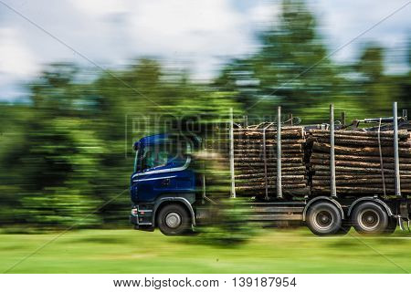 Logging truck, fully loaded. Moving fast. Blured background.